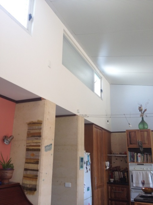 Roof/ceiling us cool room panels for weight and thermal efficiency High clerestory windows have bubble wrap for extra insulation and can open to release excess hot air Note timber at the top of the rammed earth that can be used as a picture rail.